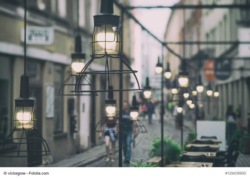 The tables with the guests, and a beautiful light of a street restaurant in the old town of Riga in the evening